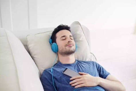 Guy with headphones on relaxes listening to music