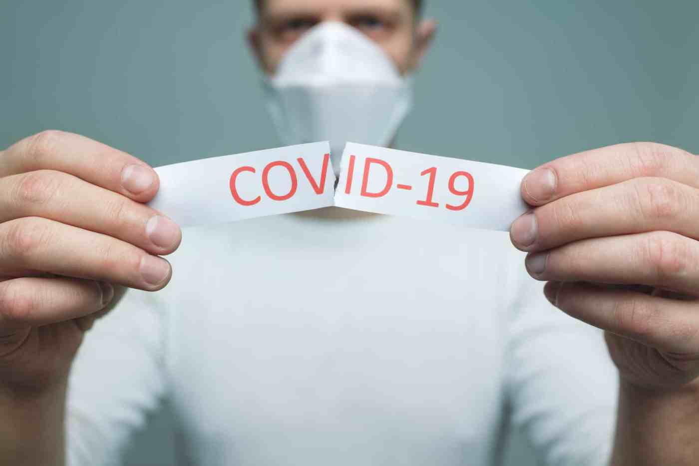 Worried man wearing a respiratory mask, holding the Coronavirus Covid-19 sign