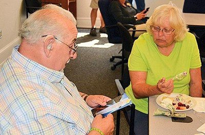 Joe Halloran looks at cards received for his retirement as his wife Kathy watches.