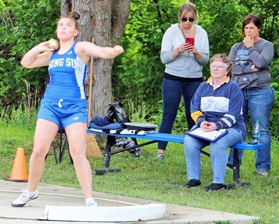 Riley Chipman concentrates in the shot put as family members watch on. Photo by Mason J. Uhlmansiek