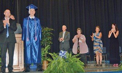 Logan Bovard gets standing ovation from superintendent Branden Roeder and school board members Gary Kinnett