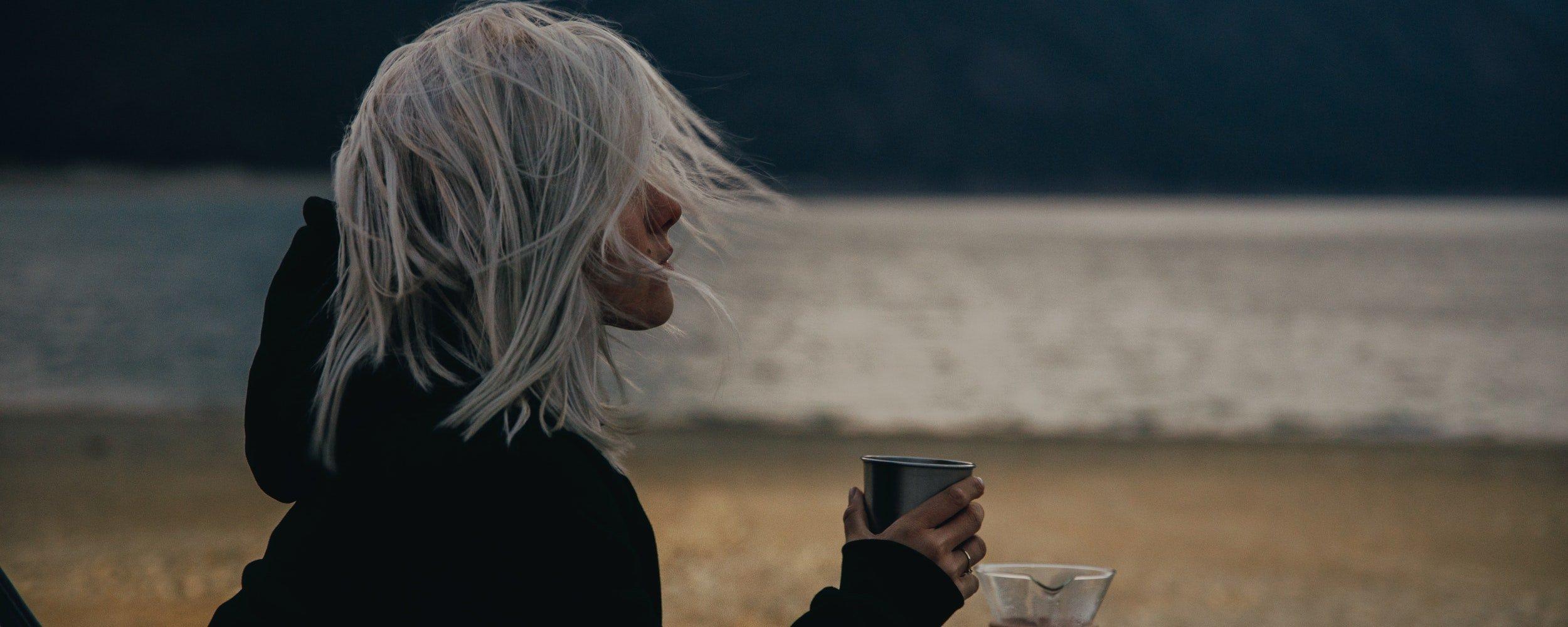 ragazza beve caffe' davanti oceano