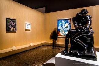In primo piano: Auguste Rodin, Il bacio bronzo; h. 85 cm; inv. 1997-48. Lyon, Musée des Beaux-Arts de Lyon. A sx: Pablo Picasso, Il bacio (1943). Olio su carta; 66 x 50 cm; inv. MP1990-77. Paris, Musée National Picasso. Sul fondo: Pablo Picasso L'abbraccio (26 settembre 1970). Olio su tela; 146 x 114 cm; inv. MP1990 -39 Paris, Musée National Picasso