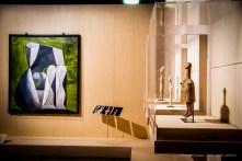 A sx: Pablo Picasso, Nudo seduto su fondo verde (1946). Pittura oleoresinosa su piastra centrale; 167 x 152 x 4 cm; inv. MPA 1946.1.8 Antibes, Musée Picasso; a dx: Idolo-campana in stile geometrico (700 a.C. circa). Terracotta; 30,5 x 15 cm; inv. CA 623 - 9800070 AGR Paris, Louvre, Départements des Antiquités greques, étrusques romaines