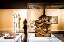In primo piano: Pablo Picasso, Musico seduto (1956). Terracotta; 74 x 52.5 cm; inv. 55971. Collezione privata; sulla sx: Pablo Picasso, Suonatore di flauto stante (1958). Assemblaggio di quindici lastre in argilla chamottata rosa; decorazioni a ingobbio; 213 x 83 x 2 cm; inv. MP3744. Paris, Musée National Picasso