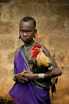 DSC_5174, Kara Tribe, Dus Village, Omo Valley, Ethiopia, 8/2013, ETHIOPIA-10306NF. A girl of the Kara tribe holds a rooster. retouched_Kate Daigneault 9/8/2013, Sam Wallander 8/11/2018