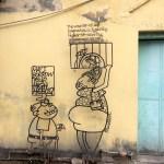 """Esta """"caricatura"""" está al lado de una prendería, locales que tenían ventanas muy altas por lo cual el señor de baja estatura le pide prestados los tacones a la señora"""