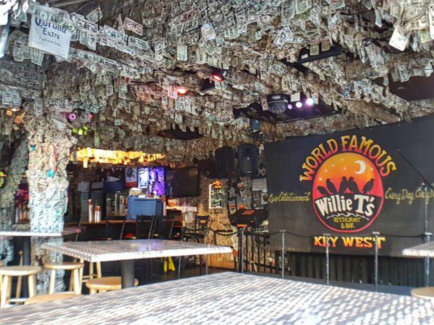 Bar com várias notas de dólares no teto.