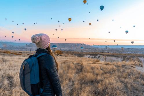 mujer viajar sola por el mundo viendo un festival de globos