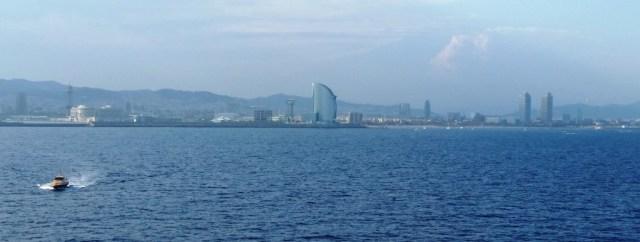 Al fondo, skyline de la ciudad de Barcelona.