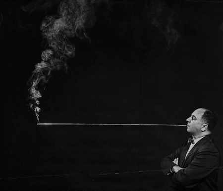 man smoking cigarette through a four-foot-long holder