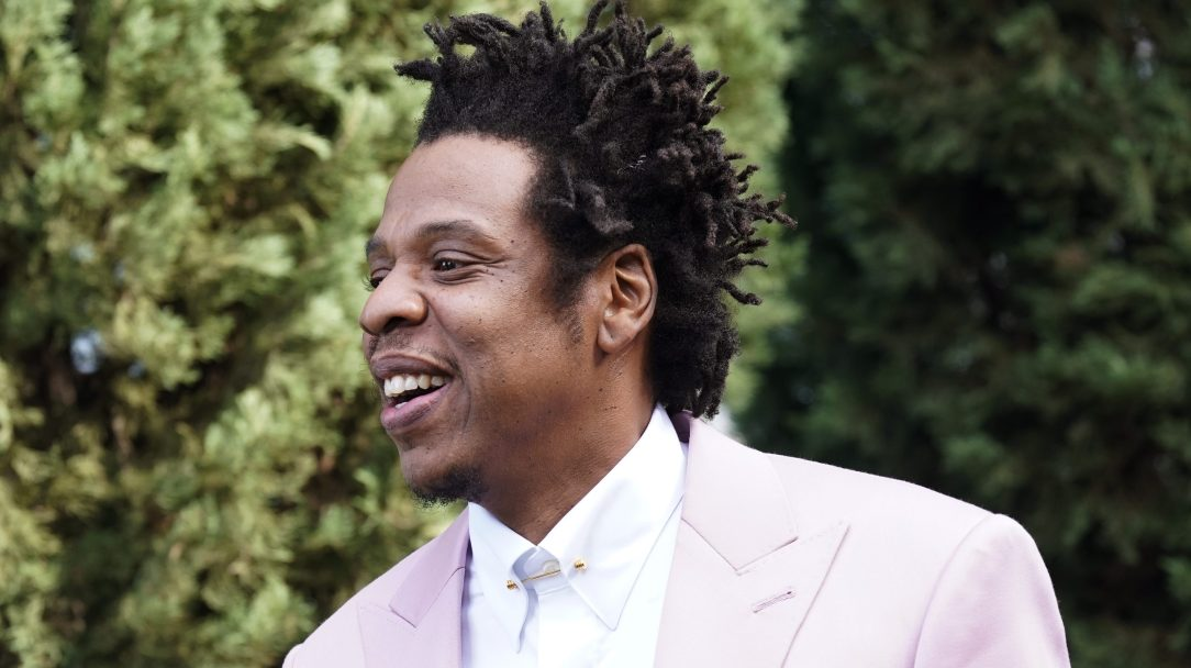 Jay-Z smiling and wearing a pink