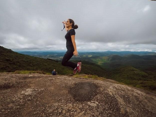 mulher pulando pedra redonda monte verde