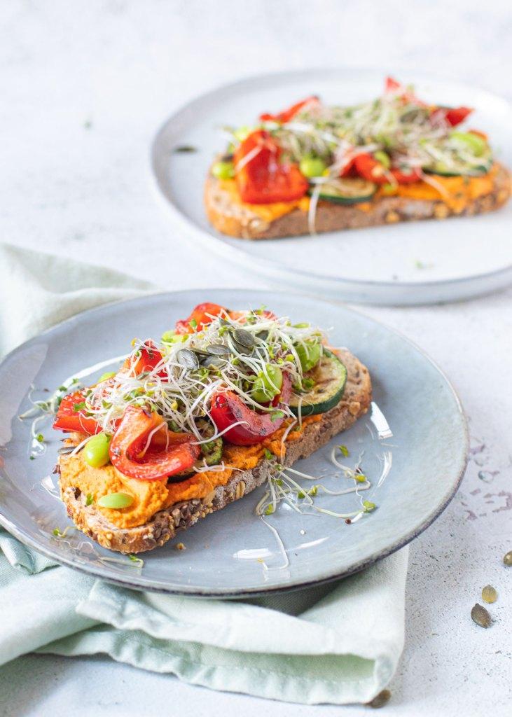 Toast met paprika hummus, gegrilde groenten, sojabonen & pompoenpitten