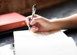 A hand holds a pen ready to write