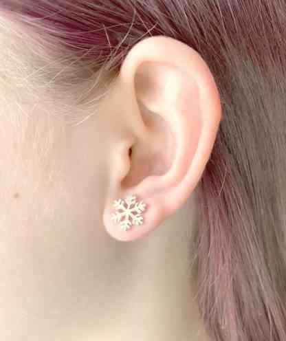 Medium size snowflake studs on ear