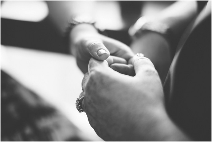 Black and white close up of a couple holding hands