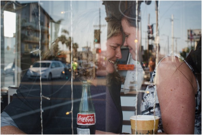 Cute engagement session idea of a couple kissing through a coffee shop window