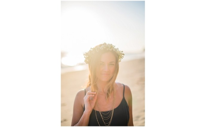 Close up portrait of a woman wearing a flower crown on a beach with sun flare in the image