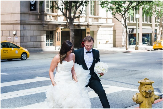 A bride and groom crossing the street in downtown LA