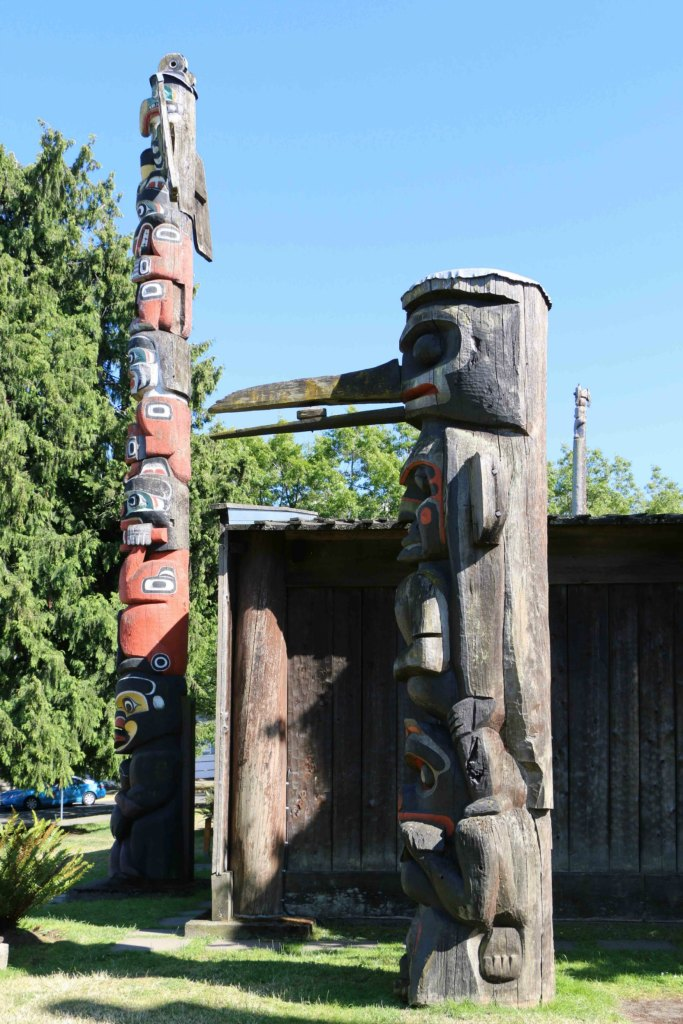 The Kwakwaka'walw Heraldic Pole (left) was carved in 1953. The Kwakwaka'walw Pole (right) was carved in 1954. (photo by Victoria Online Sightseeing Tours)