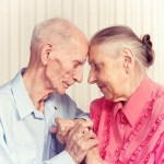 An older woman and a frail-looking man share a tender moment, putting their foreheads and hands together, as if they just talked about late-life priorities, as suggested by Being Mortal