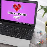 Laptop with screen showing medical record log-in page