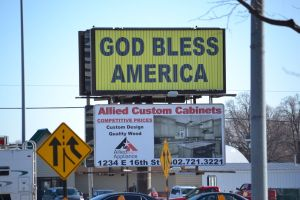 Billboard that says God bless America in black lettering with yellow background