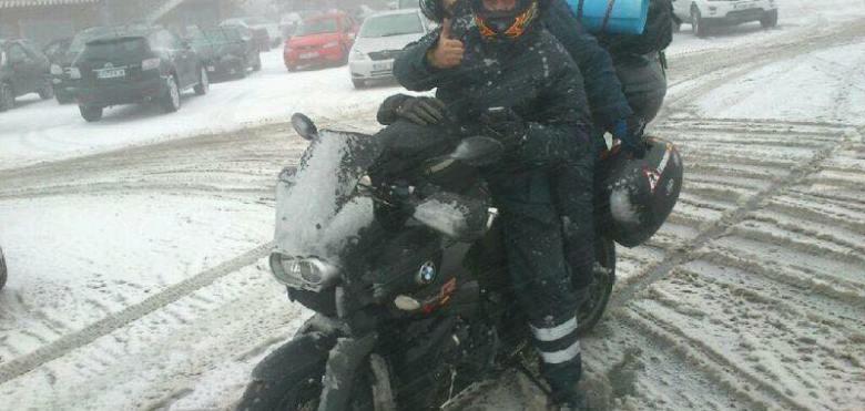 Una pareja en moto saludando sobre asfalto nevado