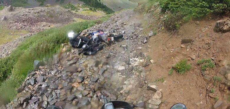 Una moto tumbada y dos personas en el suelo, sobre un camino de piedras