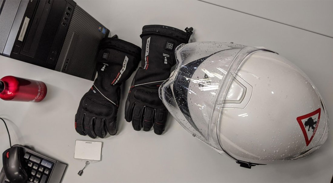 Guantes calefactables seventy degrees con casco sobre la mesa del trabajo