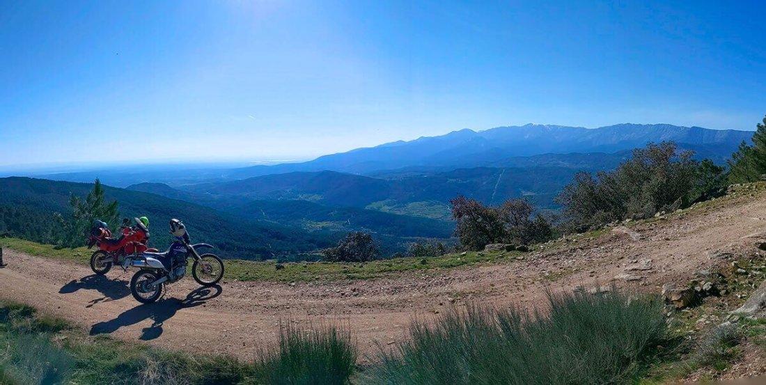Bella panorámica del norte de Gredos con dos motos en un camino