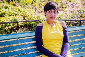 An image of the author, Khairani Barokka, sitting on a blue park bench, wearing a canary yellow dress with blue arm warmers. Khairani is looking off into the distance.