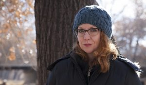 Author photo of Erin Adair-Hodges, a woman wearing glasses and red lipstick, standing in front of a tree.