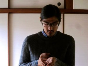 Author photo for Michael Wasson, a man with short, black hair, mustache and chin patch, his head tlited slightly downward looking at an unclear object in his hands, wearing black-framed glasses, and a dark ribbed sweater, standing in front of a white wall divided by thin wooden beams.
