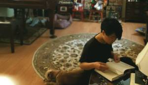 A photograph of the author, a Korean person with short hair, sitting on a round rug on the floor, reading a book. Their face is mostly obscured.