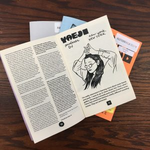 Photograph of the interior pages of a copy of Women in Sound Zine, white pages with black text and an illustration of the DJ Yaeji, a person with long dark hair and wire rim glasses with their hands clasped together above their head.