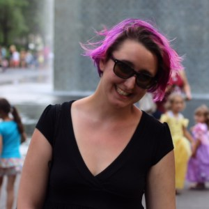 Photo of Anna Weick. A white woman with dyed pink hair and sunglasses stands outside, smiling. She is wearing a black top. Behind her, you can see kids wearing princess dresses.