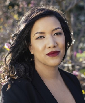 A photo of author, a woman of color with long hair and dark lipstick, in black blouse, standing outside.