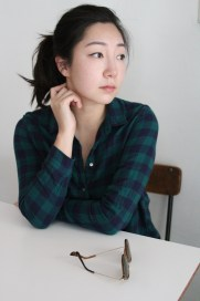 hoto of poet, EJ Koh, sitting at white table