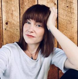 Image of the non-binary poet, Isobel O'Hare, wearing a gray blouse in front of wood background.