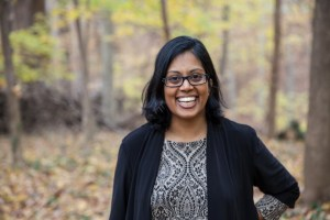 Indian American woman with dark skin, wavy hair, and black glasses smiling and standing in front of a background of trees and yellow fall foliage. She is wearing a gray patterned shirt and a black cardigan, and she has her left hand on her hip.