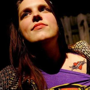 In the photo, a white woman in her late-twenties wearing a purple t-shirt is smiling while revealing a tattoo on her shoulder.