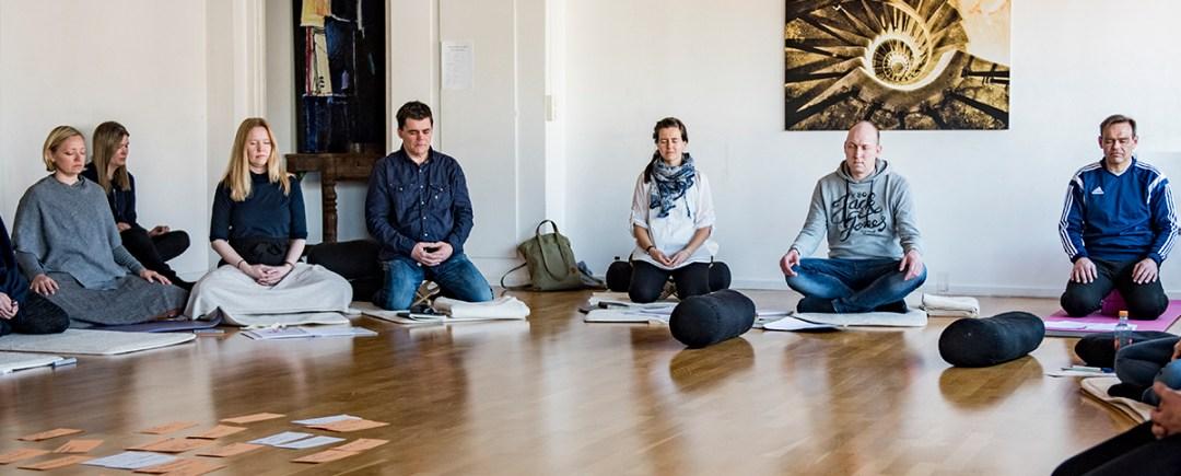 En gruppe mennesker sitter på golvet og mediterer med lukkede øyne