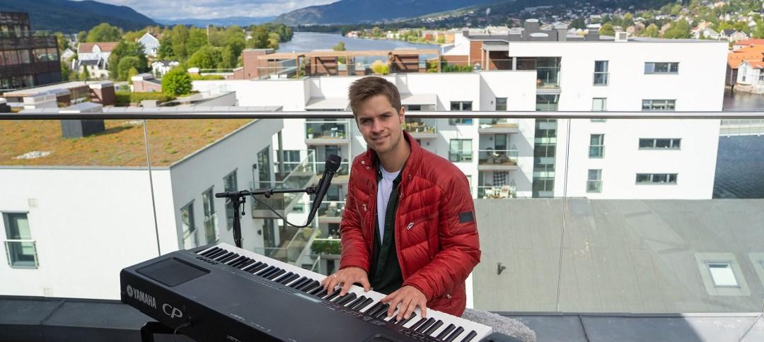 Foto av Andreas harket som spiller elpiano ute på balkongen