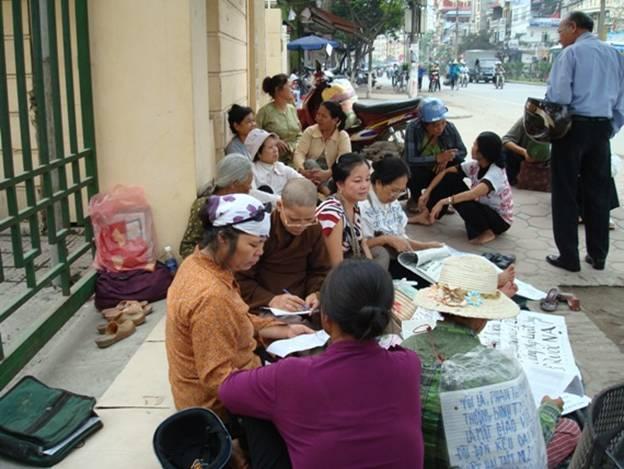 Hình Sư Bình đang ngồi trước cửa trụ sở tiếp dân, 110 Cầu Giấy, Hà Nội để viết đơn giúp Dân Oan.