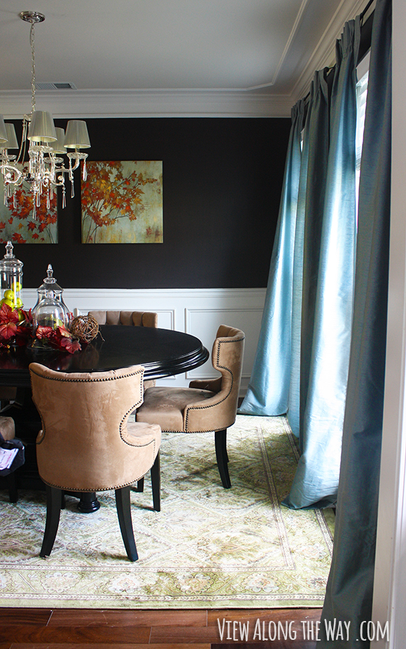 Dining room with dark walls, crown molding and chair rail at www.viewalongtheway.com