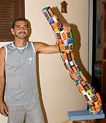 Guari em seu atelier apresentando uma de suas peças exclusivas