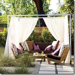 Um gazebo estar simples com cortinados para proteger do sol da tarde