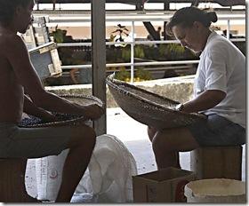 Pessoas do mercado peneirando o feijão